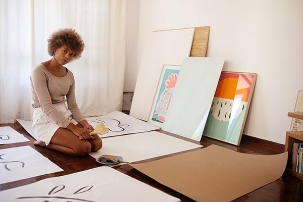 A Black artist sitting on the floor, via Pexels.com.