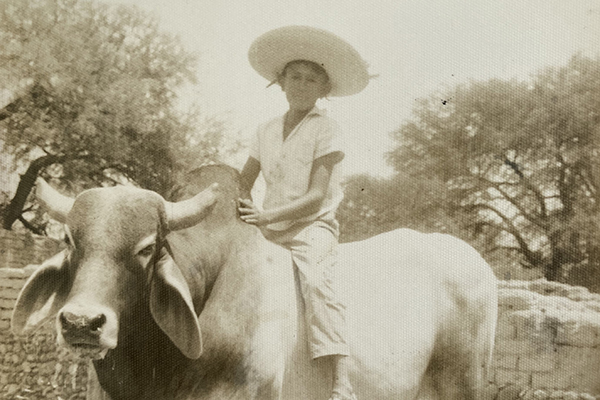 Claudia's father at 8 years old in Mexico, riding a Zebu Bull.