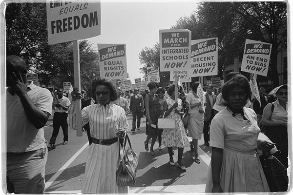 A procession of African Americans holding signs for equal freedoms, rights, housing, and schools during the March on Washington in 1963.